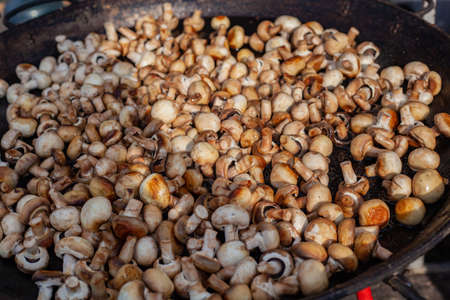 Lots of fried champignons in a large cast-iron skillet in the open air