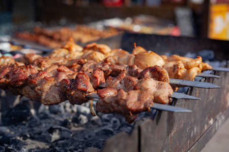 Meat on a skewer is fried on hot charcoal on an iron barbecue.