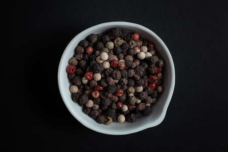 Peppercorn pepper spice in a white ceramic bowl isolated on black background