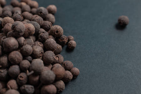 Spice allspice black peppercorns scattered on a black background