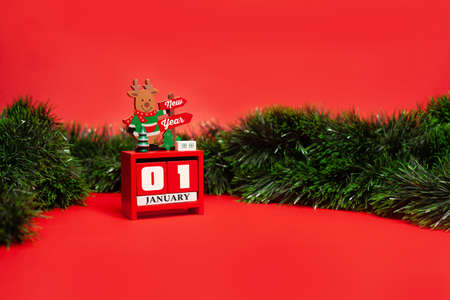 Decorative Christmas deer stands on a calendar with the inscription Happy New Year on a red background with green tinsel