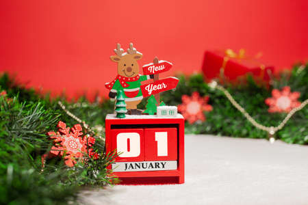 Decorative  Christmas deer stands on a calendar with the inscription Happy New Year on a red background with green tinsel decorated with Christmas toys and snow