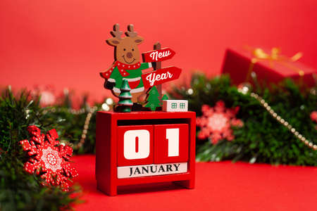 Decorative Christmas deer stands on a calendar with the inscription Happy New Year on a red background with green tinsel decorated with Christmas toys