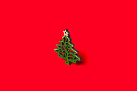 Decorative Christmas tree with green patterns with a star on top isolated on a red background