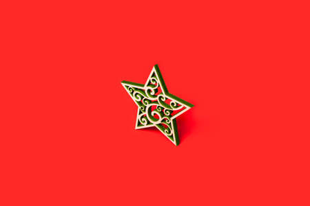 Decorative Christmas star made of wood with green patterns isolated on red background