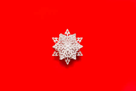 Volume white snowflake in sparkles on a red background