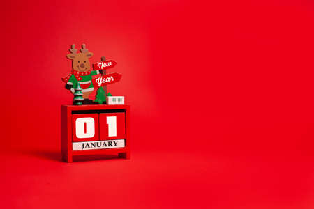 Decorative Christmas deer stands on a calendar with the inscription Happy New Year on a red background