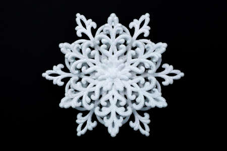 White decorative snowflake in sparkles isolated on black background
