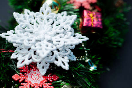 Christmas wreath decorated with a white snowflake, cones, red ball, red snowflake and beads on a black background