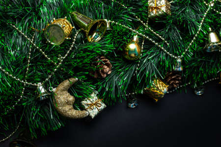 Christmas wreath decorated with golden balls, bells, gifts and decorative reels on a black background Stockfoto