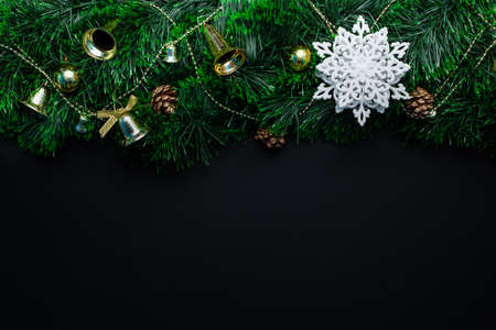 Christmas wreath decorated with a white snowflake and golden bells, balls, cones on a black background. Stockfoto