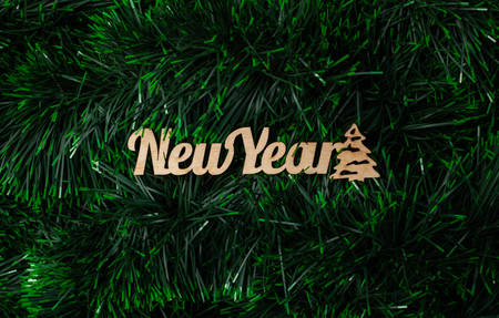 Inscription New Year made of wooden letters and silhouette of a Christmas tree on a green background from tinsel