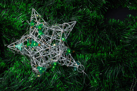 Silver vine star decorated with a Christmas tree garland on a green tinsel background Stockfoto