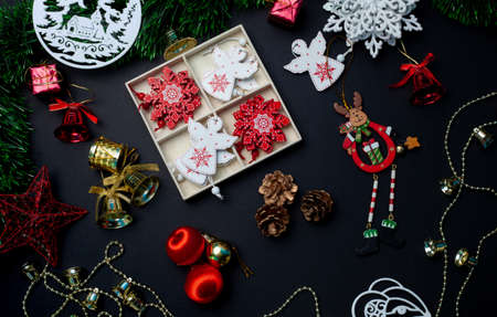 Christmas toys and decorations with red balls, stars, bells and snowflakes on a black background