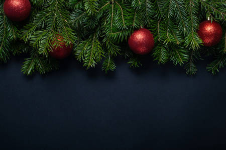 Red balls among Christmas tree branches on a black background with place for text. Stockfoto