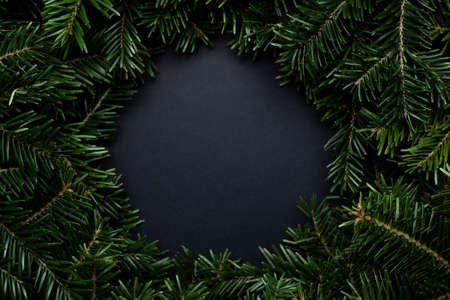 Wreath of Christmas tree branches with a black place for text in the middle