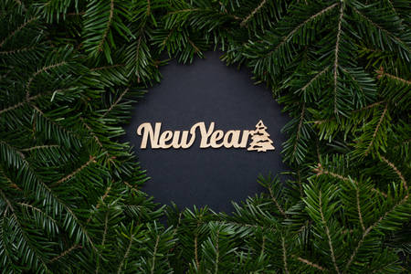 Wreath of Christmas tree branches with the inscription New Year in the center on a black background