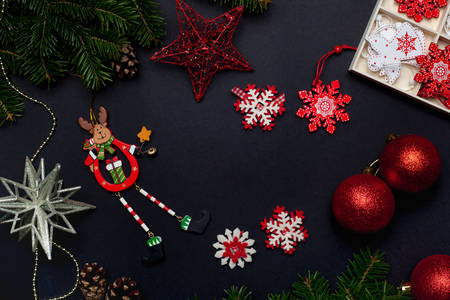 Juguetes y adornos navideños con bolas, estrellas, campanas y copos de nieve sobre un fondo negro