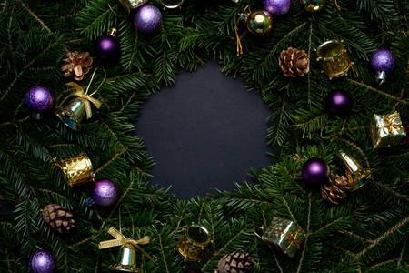 Christmas wreath decorated with purple and gold toys with a black background in the middle