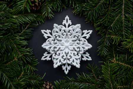 wreath of fir branches decorated with cones and a white decorative snowflake in the center