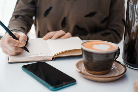 Girl writes I love you in a notebook on a table next to a phone and a cup of coffee decorated with a heart and rosebuds