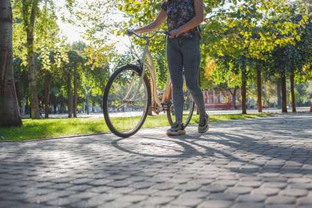 A girl in jeans and sneakers stands next to a beige bicycle in a park among green trees and a lawn