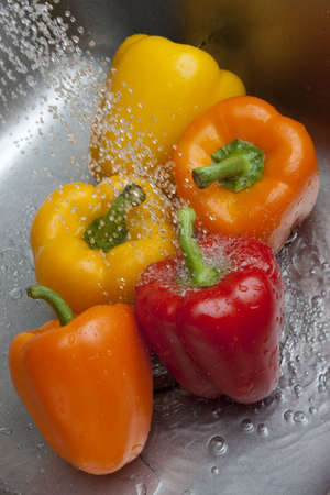 Yellow, red, and orange bell peppers with water rinsing over them in metal sink