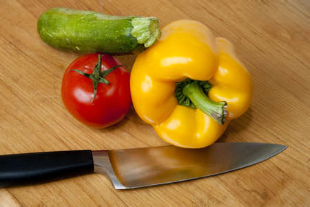 Bell pepper, tomato, and zuchini squash with knife on cutting board photo