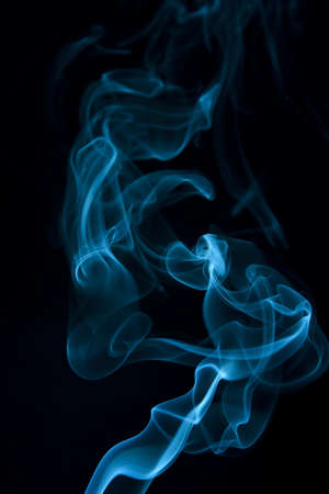 wisp: Teal smoke wisp rising against  black background