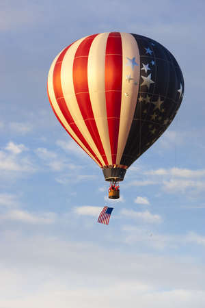 American flag pattern hot air balloon sailing across blue sky with American flag hanging beneath basket Archivio Fotografico