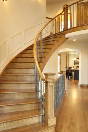 All wood curved staircase with hallway and kitchen in view.