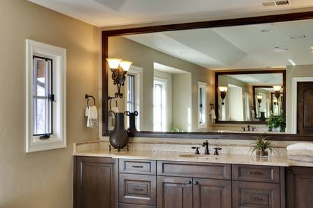 custom cabinet: Bathroom with large his and hers sinks visible in main view and reflection.