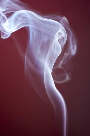 White blue smoke rising vertically against spot lit maroon background photo