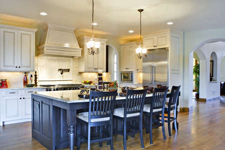 kitchen island: Kitchen from angle showing center island, stove (in background) and hallway. Stock Photo