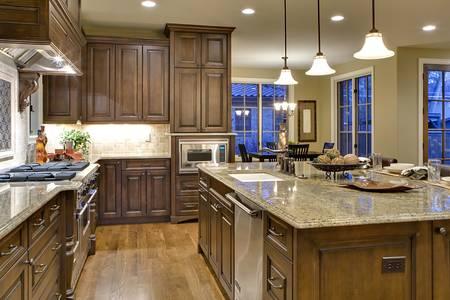 バトラーのパントリーの観点からキッチン。料理島、流し、範囲および石および隅を示します。