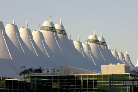 Denver International Airport at dawn with sunlight hitting peaks