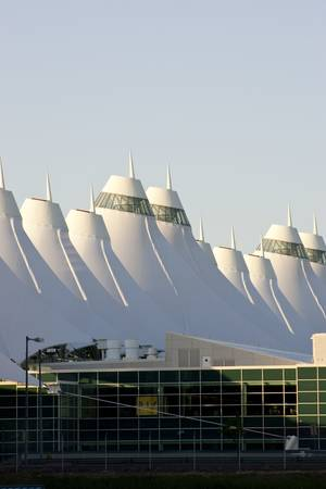 Denver International Airport at dawn with sunlight hitting peaks