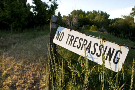 trespass: No Trespassing sign posted on barb wire fence