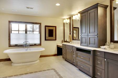 Angled view of bathroom with tub and cabinetry