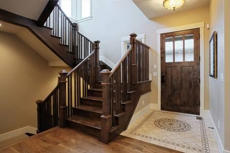木製の階段とフローリングのエレガントなホーム ホワイエ