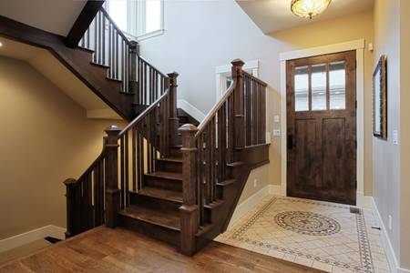 Foyer: Elegant home foyer with wood stairs and flooring
