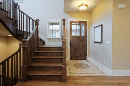 Elegant home foyer with wood stairs and flooring photo