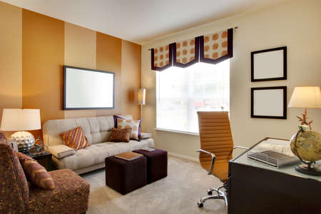guest house: Small office space room with orange accent walls and desk Stock Photo