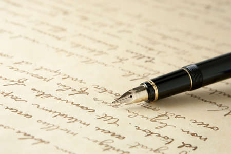 copy writing: Gold Fountain Pen on Written Page. Crisp focus on nib of pen.