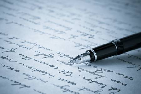 nib: Blue Toned Image of Gold Fountain Pen on Written Page. Crisp focus on nib of pen. Stock Photo