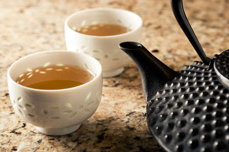 Warm morning lighting. Close up of tetsubin tea pot and cups on granite surface. Focus on tip of tea pot spout.