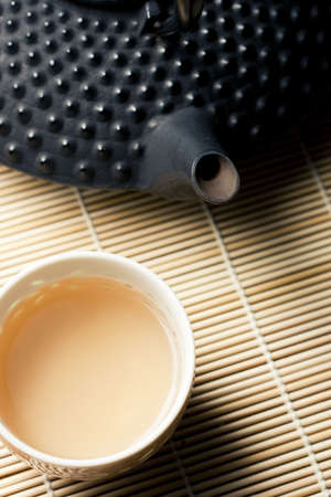 tetsubin: Warm morning lighting. Close up of tetsubin tea pot and cups on granite surface. Focus on tip of tea pot spout.