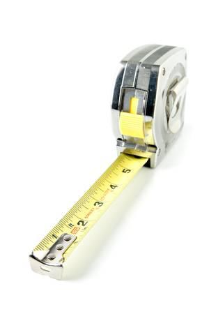 白い背景の上のテープを測定します。テープの端を測定のヒントに焦点を当てます。