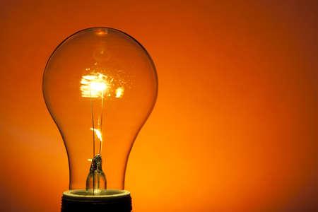 Incandescent Light Bulb on Orange. Spot lit background. Studio lit. Imagens