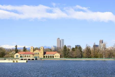 denver skyline with mountains: Denver Skyline from City Park and Lake. Focus on Foreground building Stock Photo